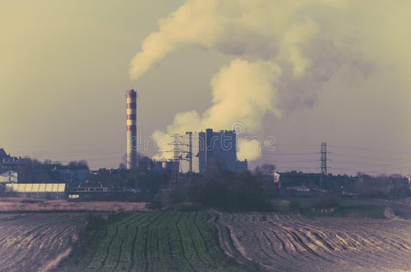 Καπνίζοντας χοάνες ενός σταθμού παραγωγής ηλεκτρικού ρεύματος κοντά σε ένα καλλιεργήσιμο έδαφος στοκ φωτογραφία