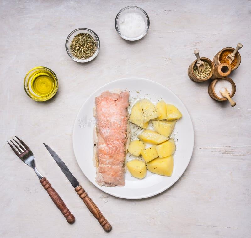 Καπνισμένα ψάρια, με τις πατάτες και τον άνηθο σε ένα άσπρο πιάτο, με τα καρυκεύματα, την ξύλινη αγροτική τοπ άποψη υποβάθρου μαχ στοκ εικόνες