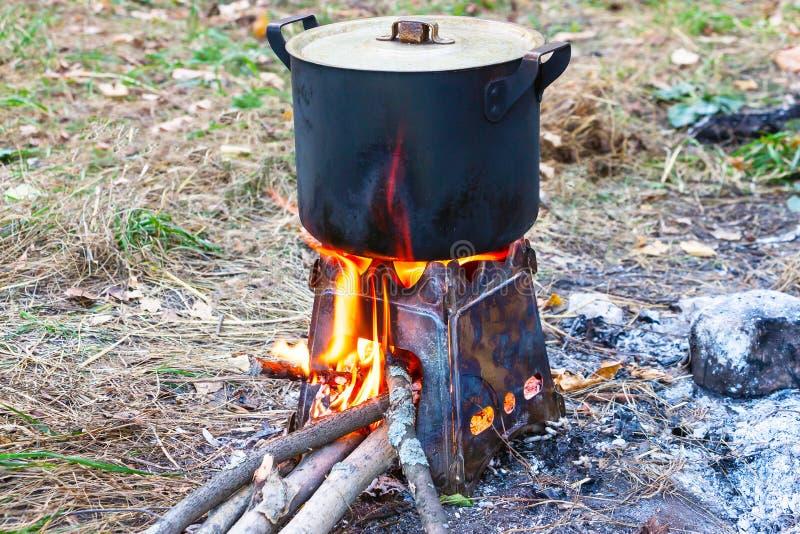 Καπνισμένο δοχείο σε μια σόμπα στρατόπεδων στοκ εικόνες