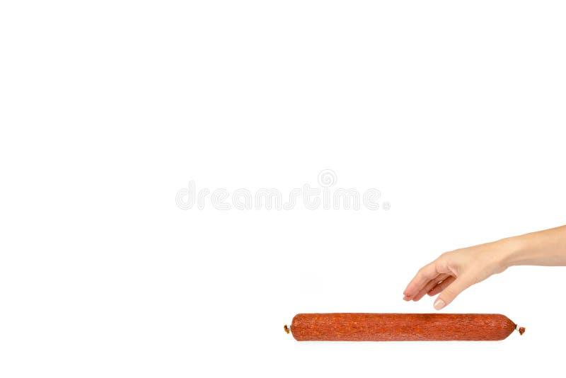 καπνισμένο κομμάτι λουκάνικων σαλαμιού με το χέρι, που απομονώνεται στο άσπρο υπόβαθρο, διαστημικό πρότυπο αντιγράφων στοκ φωτογραφία με δικαίωμα ελεύθερης χρήσης