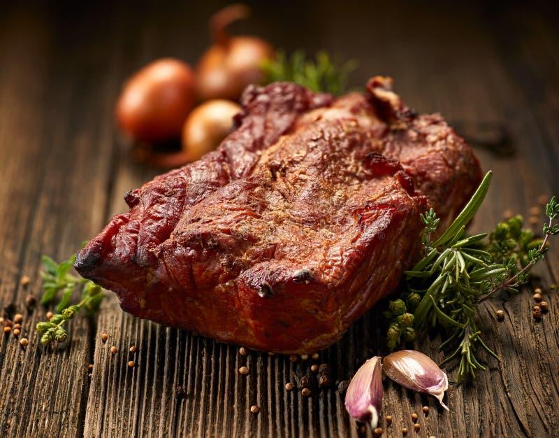 Καπνισμένο κρέας, καπνισμένη οσφυϊκή χώρα χοιρινού κρέατος σε έναν ξύλινο πίνακα με την προσθήκη των φρέσκων χορταριών και των αρ στοκ φωτογραφία με δικαίωμα ελεύθερης χρήσης