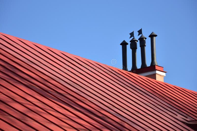 Καπνοδόχοι κινηματογραφήσεων σε πρώτο πλάνο στην κόκκινους στέγη και τον ουρανό στοκ φωτογραφία