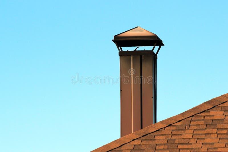 Καπνοδόχος μετάλλων στη στέγη ενάντια στο μπλε ουρανό στοκ εικόνα με δικαίωμα ελεύθερης χρήσης