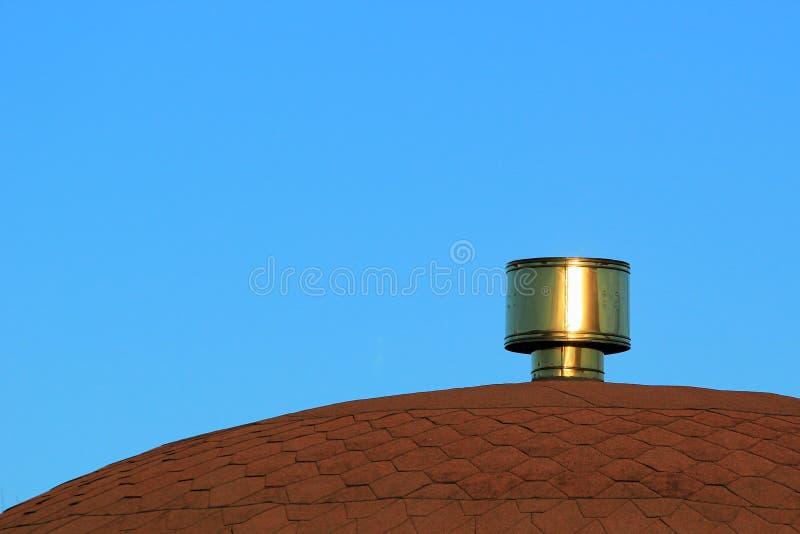 Καπνοδόχος μετάλλων στη στέγη ενάντια στο μπλε ουρανό στοκ φωτογραφία με δικαίωμα ελεύθερης χρήσης