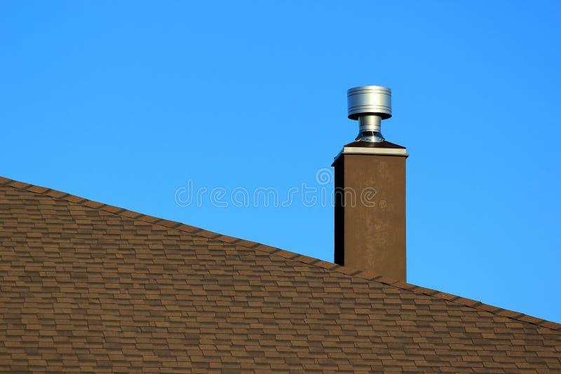 Καπνοδόχος μετάλλων στη στέγη ενάντια στο μπλε ουρανό στοκ φωτογραφίες