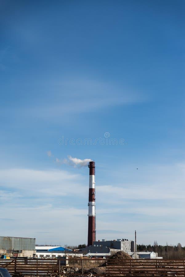 Καπνοδόχος εργοστασίων που απελευθερώνει τον άσπρο καπνό στοκ εικόνες