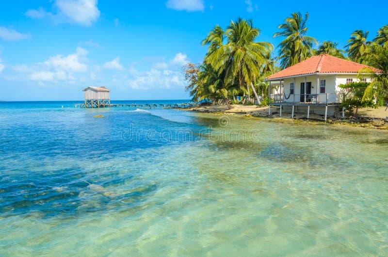 Καπνός Caye - που χαλαρώνει στην καμπίνα ή το μπανγκαλόου στο μικρό τροπικό νησί στο σκόπελο εμποδίων με την παραλία παραδείσου,  στοκ φωτογραφίες