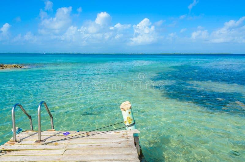 Καπνός Caye - που χαλαρώνει στην ξύλινη αποβάθρα στο μικρό τροπικό νησί στο σκόπελο εμποδίων με την παραλία παραδείσου, καραϊβική στοκ φωτογραφίες με δικαίωμα ελεύθερης χρήσης