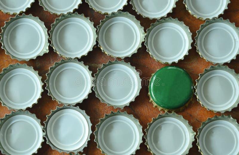 ΚΑΠ μπουκαλιών κασσίτερου για την μπύρα ή τη σόδα κάλυψης που τακτοποιεί στον ξύλινο πίνακα στοκ φωτογραφίες