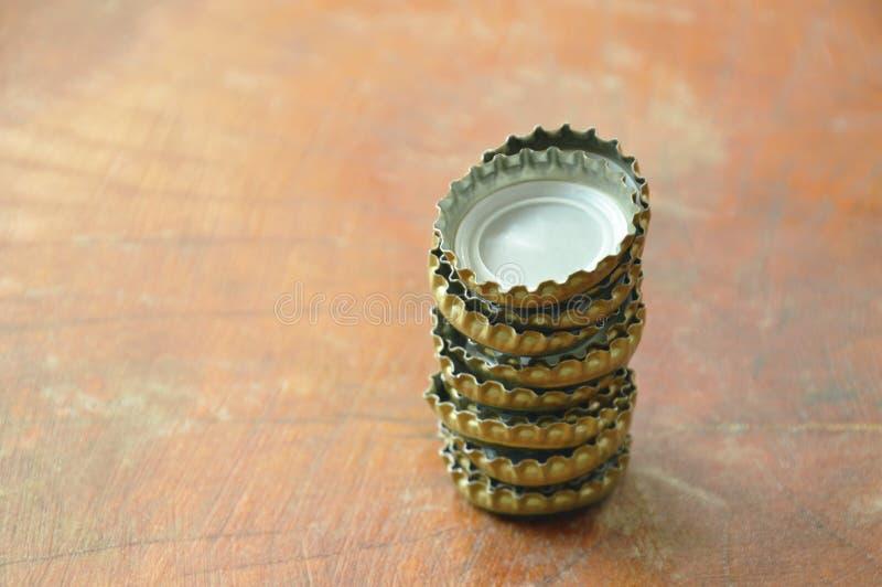 ΚΑΠ μπουκαλιών κασσίτερου για την μπύρα ή τη σόδα κάλυψης που τακτοποιεί στον ξύλινο πίνακα στοκ εικόνα με δικαίωμα ελεύθερης χρήσης