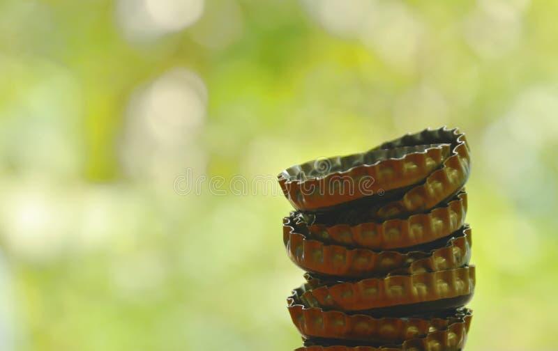 ΚΑΠ μπουκαλιών κασσίτερου για την μπύρα ή τη σόδα κάλυψης που τακτοποιεί στο υπόβαθρο κήπων στοκ εικόνες
