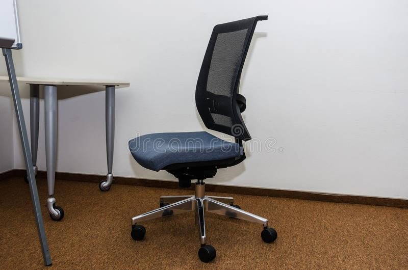 Καρέκλα γραφείων κοντά στον πίνακα και το μέρος ενός flipchart στοκ φωτογραφία