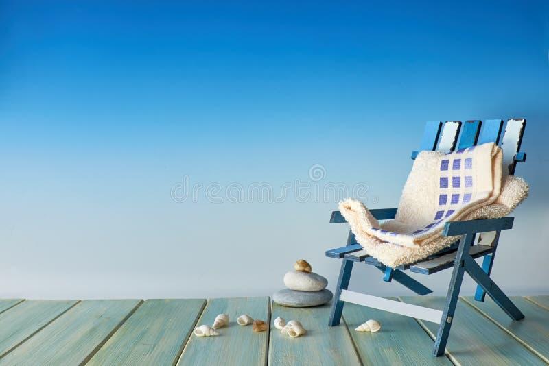Καρέκλα παραλιών στο ξύλινο πεζούλι με τα κοχύλια θάλασσας, decoratio παραλιών στοκ εικόνες