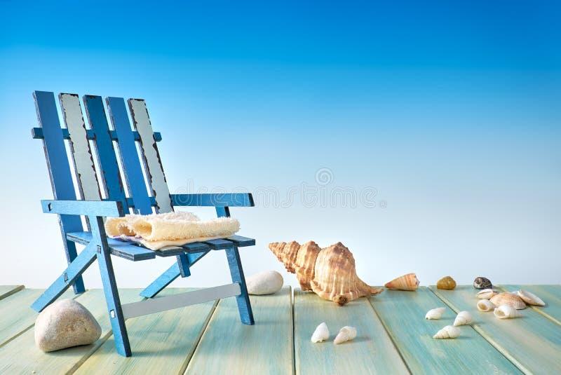 Καρέκλα παραλιών στο ξύλινο πεζούλι με τα κοχύλια θάλασσας, decoratio παραλιών στοκ φωτογραφίες