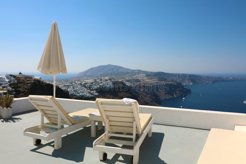 Καρέκλες και ομπρέλα γεφυρών στο πεζούλι του ξενοδοχείου θερέτρου πολυτέλειας με την άποψη θάλασσας Άσπρη αρχιτεκτονική με το μόν στοκ φωτογραφία με δικαίωμα ελεύθερης χρήσης