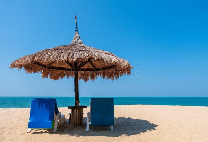 Καρέκλες και ομπρέλα παραλιών ζεύγους στην τροπική παραλία με το υπόβαθρο θάλασσας και μπλε ουρανού στοκ εικόνα