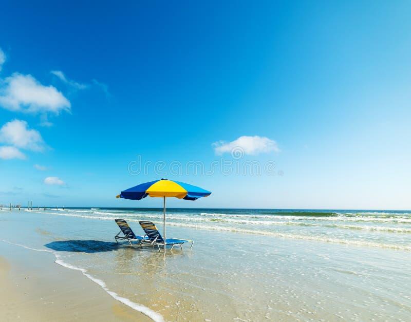 Καρέκλες και parasol παραλιών στην άμμο στην ακτή Daytona Beach στοκ φωτογραφία με δικαίωμα ελεύθερης χρήσης