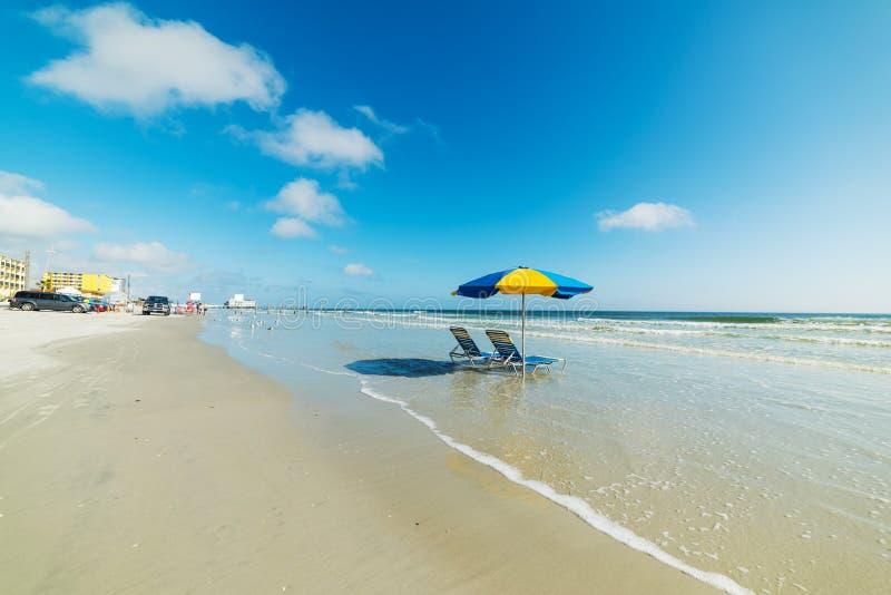 Καρέκλες και parasol παραλιών στην άμμο στην ακτή Daytona Beach στοκ εικόνα με δικαίωμα ελεύθερης χρήσης