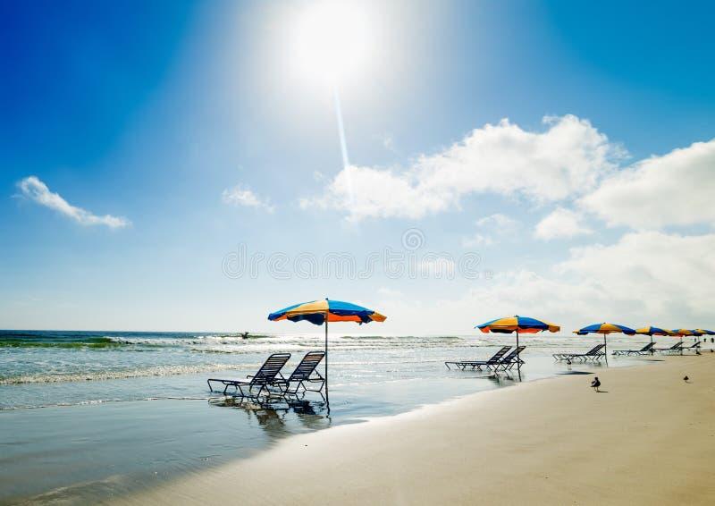 Καρέκλες παραλιών και parasols σε Daytona Beach κάτω από έναν λάμποντας ήλιο στοκ εικόνες