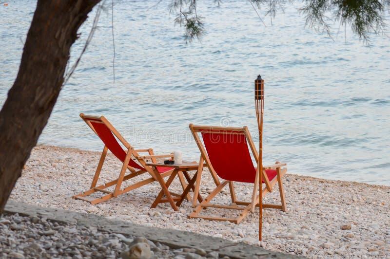 Καρέκλες παραλιών στο υπόβαθρο ηλιοβασιλέματος στην αδριατική θάλασσα στοκ φωτογραφία