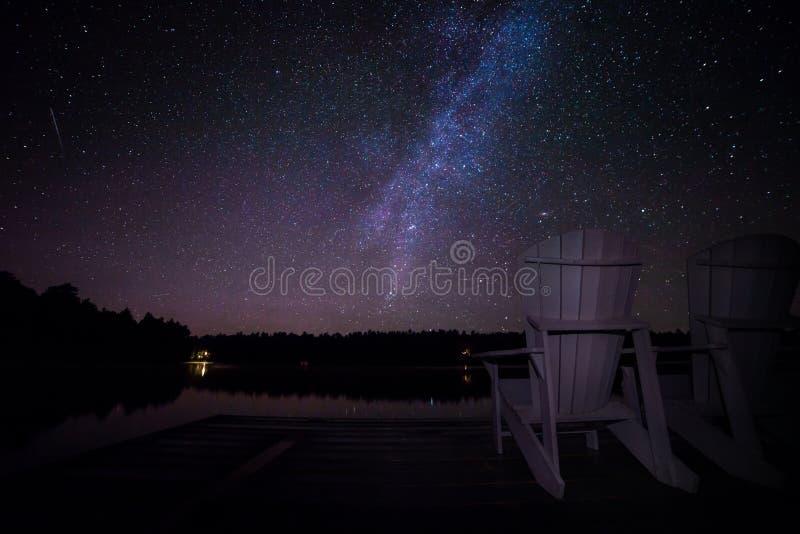 καρέκλες muskoka σε μια αποβάθρα τη νύχτα με το γαλακτώδη τρόπο στο υπόβαθρο στοκ φωτογραφία με δικαίωμα ελεύθερης χρήσης