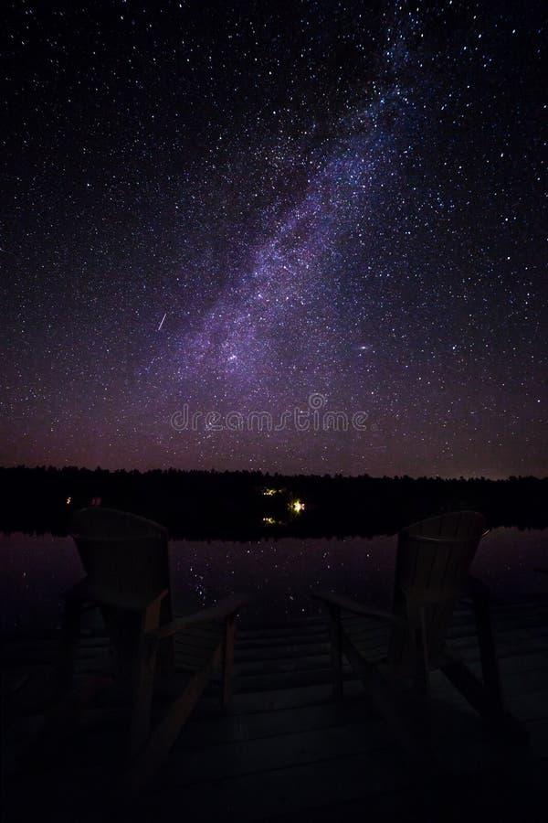 καρέκλες muskoka σε μια αποβάθρα τη νύχτα με το γαλακτώδη τρόπο στο υπόβαθρο στοκ φωτογραφίες με δικαίωμα ελεύθερης χρήσης