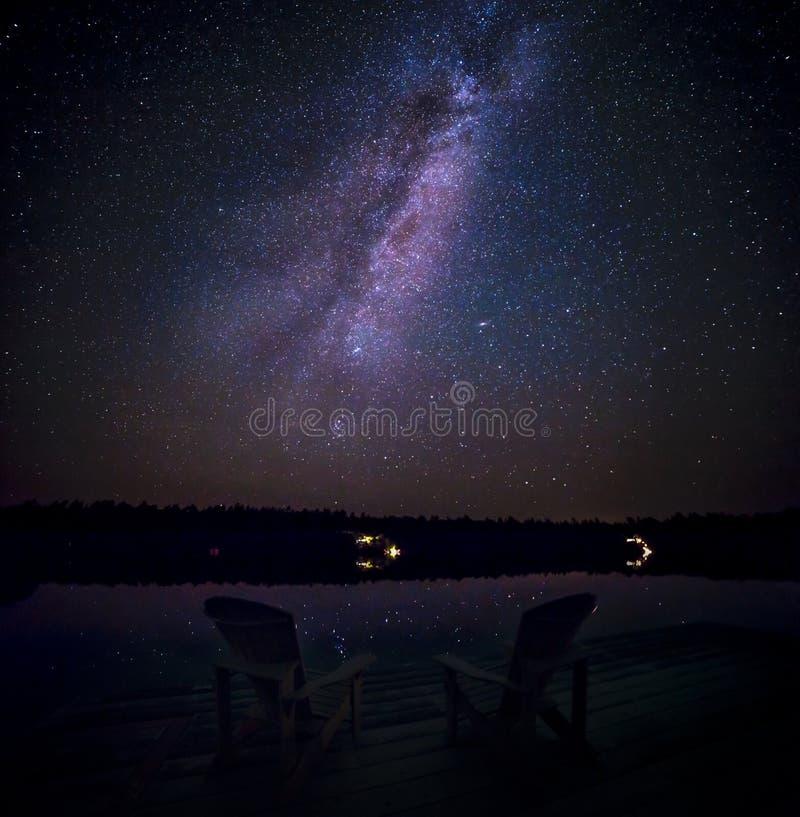 καρέκλες muskoka σε μια αποβάθρα τη νύχτα με το γαλακτώδη τρόπο στο υπόβαθρο στοκ εικόνες