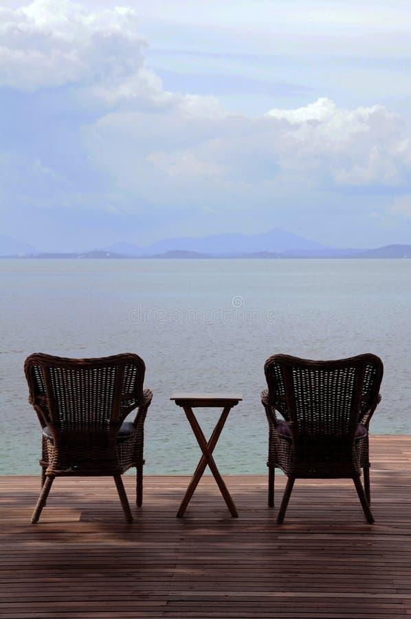 Καρέκλα βραχιόνων στο πεζούλι στην παραλία στοκ εικόνες