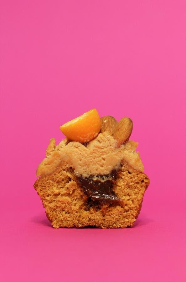 Καραμέλα κρέμας cupcake στο ρόδινο υπόβαθρο που διακοσμείται από τα αμύγδαλα στοκ εικόνα