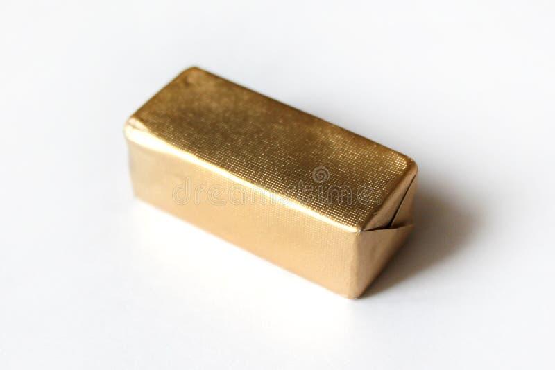 Καραμέλα σοκολάτας ορθογωνίων που τυλίγεται στο χρυσό φύλλο αλουμινίου που απομονώνεται στην άσπρη επιφάνεια στοκ φωτογραφίες με δικαίωμα ελεύθερης χρήσης