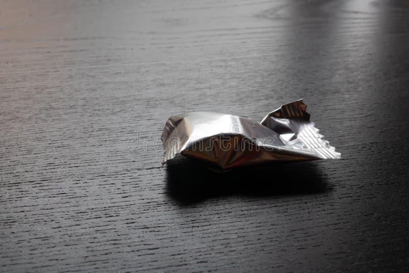 Καραμέλα στην ασημένια συσκευασία αλουμινίου στο μαύρο υπόβαθρο - εικόνα στοκ φωτογραφία