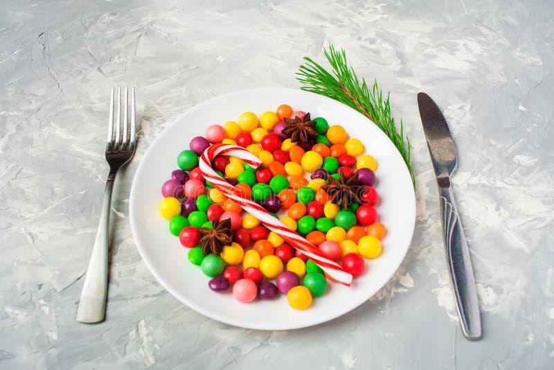 Καραμέλες στο πιάτο με flatware όπως την ανθυγειινή έννοια τροφίμων, chri στοκ εικόνες