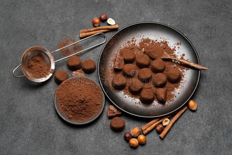 Καραμέλες τρουφών σοκολάτας και σκόνη κακάου στο σκοτεινό συγκεκριμένο υπόβαθρο στοκ φωτογραφία με δικαίωμα ελεύθερης χρήσης