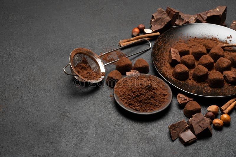 Καραμέλες τρουφών σοκολάτας και σκόνη κακάου στο σκοτεινό συγκεκριμένο υπόβαθρο στοκ εικόνες