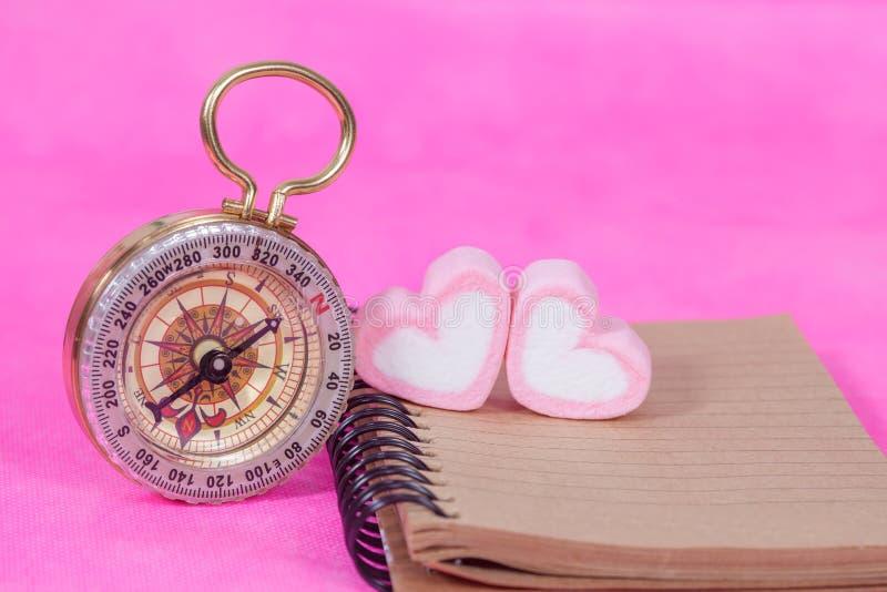 Καραμέλες καρδιών με τη σημείωση βιβλίων και την πυξίδα, έγγραφο μηνυμάτων στοκ φωτογραφία