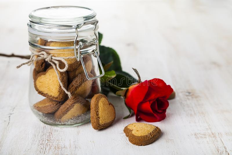 Καρδιά-διαμορφωμένα μπισκότα σε ένα βάζο γυαλιού και κόκκινα τριαντάφυλλα στοκ φωτογραφία με δικαίωμα ελεύθερης χρήσης