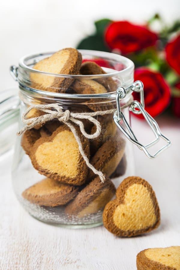 Καρδιά-διαμορφωμένα μπισκότα σε ένα βάζο γυαλιού και κόκκινα τριαντάφυλλα στοκ εικόνες