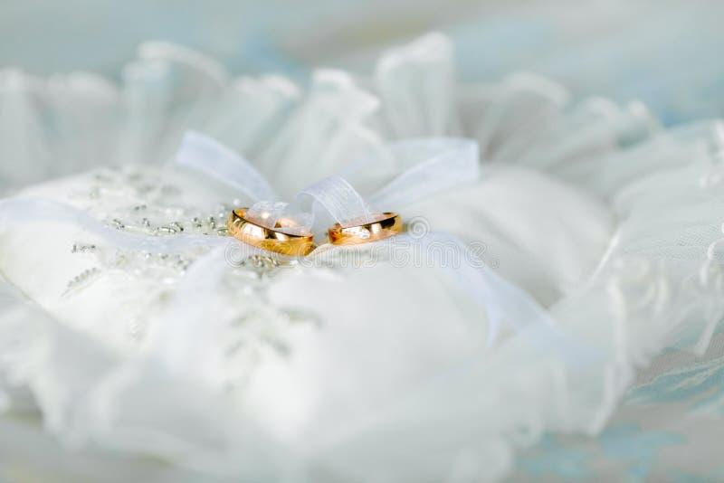 Καρδιά-διαμορφωμένο μαξιλάρι με τα γαμήλια χρυσά δαχτυλίδια στοκ εικόνες με δικαίωμα ελεύθερης χρήσης