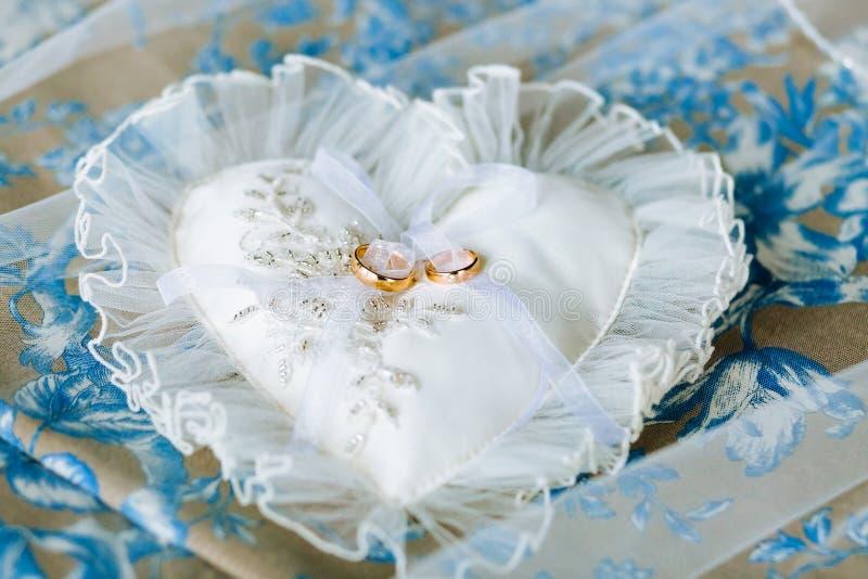 Καρδιά-διαμορφωμένο μαξιλάρι με τα χρυσά δαχτυλίδια δαντελλών και γάμου σιφόν στοκ εικόνα