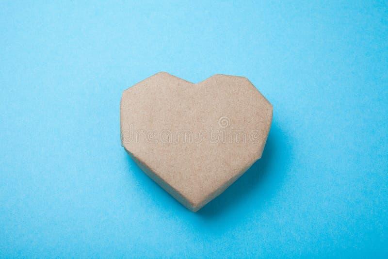 Καρδιά εγγράφου που γίνεται από το ανακυκλωμένο έγγραφο για ένα μπλε υπόβαθρο στοκ φωτογραφία με δικαίωμα ελεύθερης χρήσης