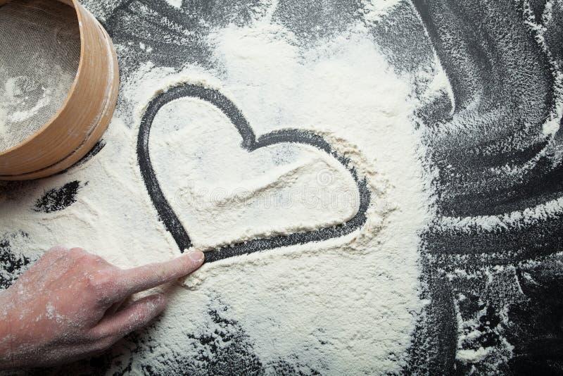 Καρδιά και σύμβολο της αγάπης, που χρωματίζονται στο αλεύρι, με το χέρι μιας γυναίκας στοκ φωτογραφίες