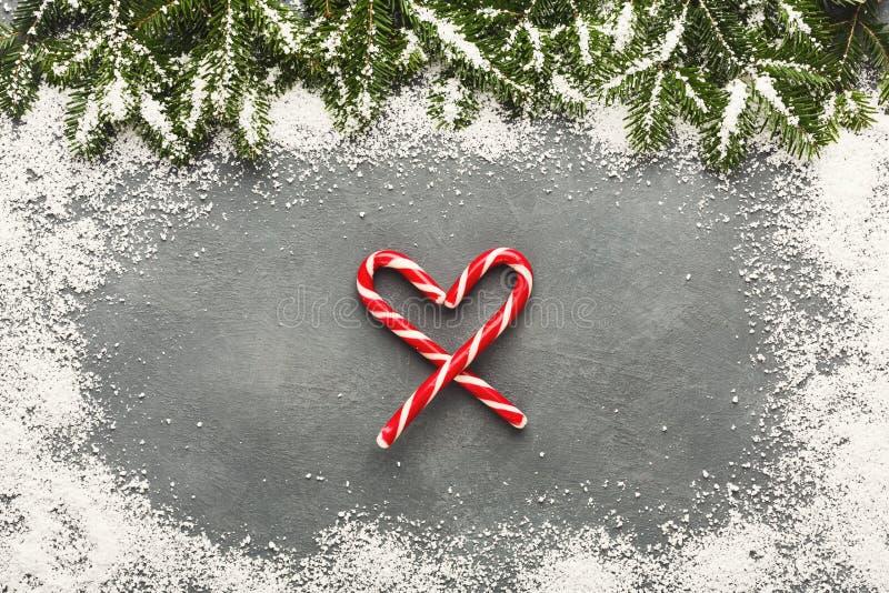 Καρδιά καλάμων καραμελών ζάχαρης Χριστουγέννων στον γκρίζο πίνακα στοκ φωτογραφία