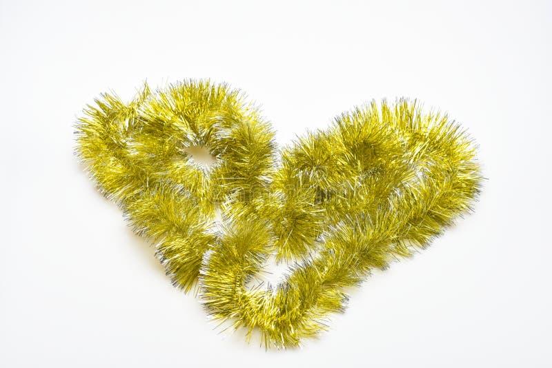 Καρδιά που γίνεται από χρυσό tinsel στο άσπρο υπόβαθρο Έννοια συμβόλων αγάπης Μορφή του συμβόλου αγάπης που γίνεται από το λαμπύρ στοκ φωτογραφία