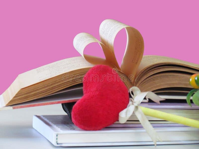 Καρδιά που διαμορφώνεται φιαγμένη από παλαιές σελίδες βιβλίων και κόκκινη καρδιά σελιδοδεικτών που απομονώνονται στο ρόδινο υπόβα στοκ φωτογραφία