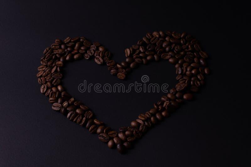 Καρδιά που ευθυγραμμίζεται με τα σιτάρια του καφέ σε μια σκοτεινή τοπ άποψη υποβάθρου στοκ φωτογραφία με δικαίωμα ελεύθερης χρήσης