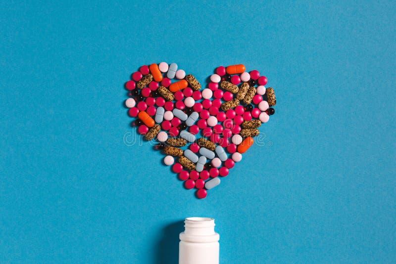 Καρδιά συμβόλων από το φάρμακο χαπιών χρώματος στο μπλε υπόβαθρο Έννοια ιατρικής δημιουργικότητας στοκ εικόνες με δικαίωμα ελεύθερης χρήσης