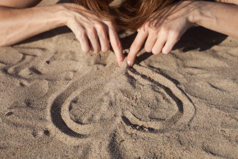 Καρδιά σχεδίων κοριτσιών στην άμμο, θερινή έννοια στοκ εικόνες