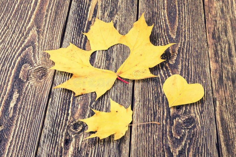 Καρδιά του κίτρινου φύλλου σφενδάμου στο ξύλινο υπόβαθρο στοκ φωτογραφία με δικαίωμα ελεύθερης χρήσης