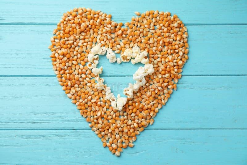 Καρδιά φιαγμένη από εύγευστους popcorn και πυρήνες στο ξύλινο υπόβαθρο στοκ φωτογραφία με δικαίωμα ελεύθερης χρήσης