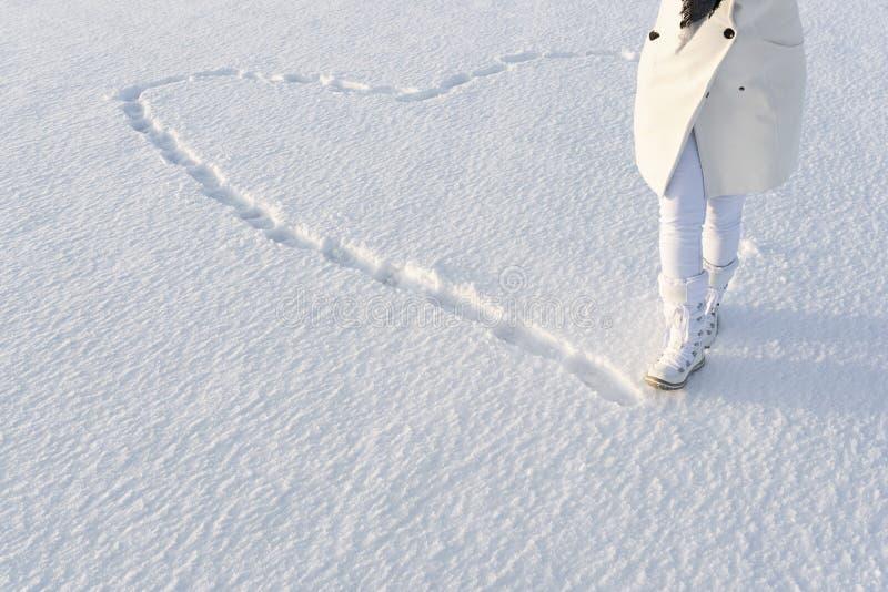 Καρδιά χιονιού που γίνεται από τα βήματα Ανώνυμη γυναίκα στο άσπρο χειμερινό παλτό, περίπατοι στο χιόνι στις μπότες χιονιού στοκ εικόνες με δικαίωμα ελεύθερης χρήσης